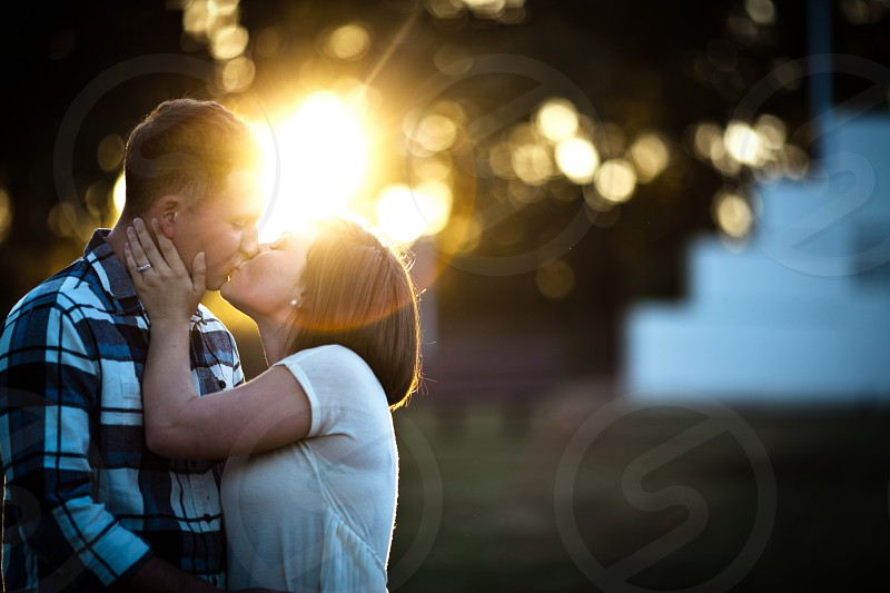 Couple kissing at sunset photo