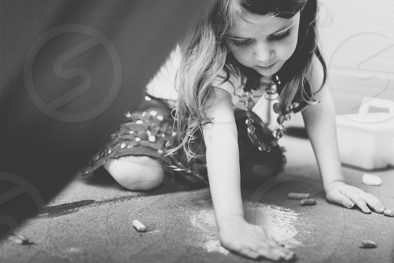 girl playing with chalk on the ground photo