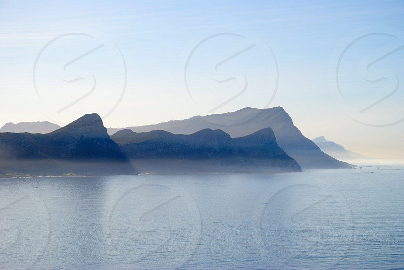 mountain range silhouette beside body of water photo