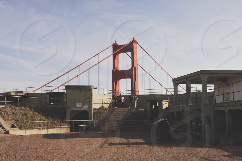 golden gate bridge across building roof with people on it photo