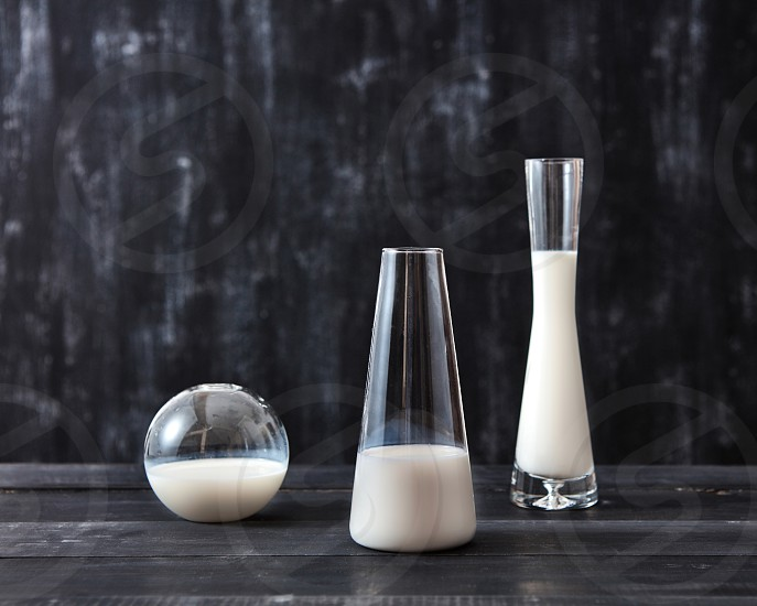 White milk in the glass vases on a dark wooden table on a back with copy space. Milk saving concept photo