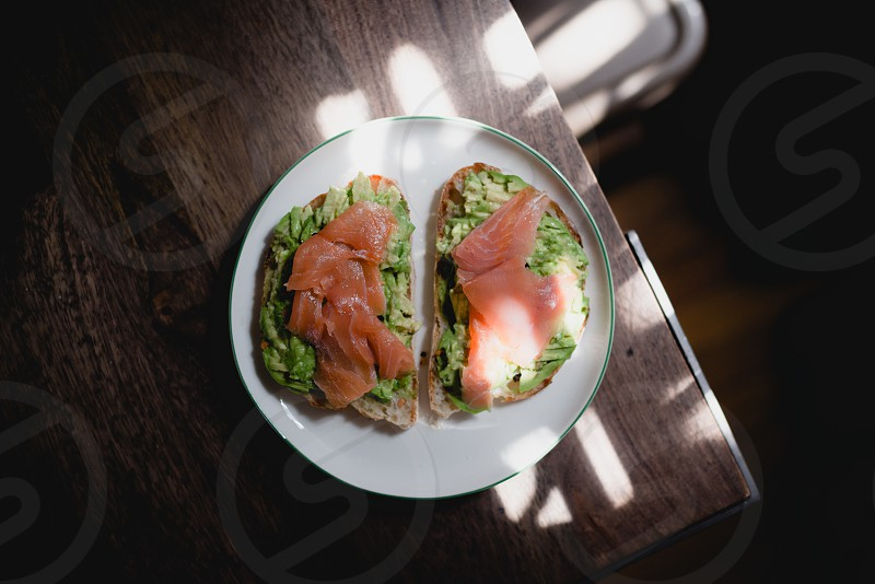 Avocado toast topped with smoked salmon under pretty lights  photo