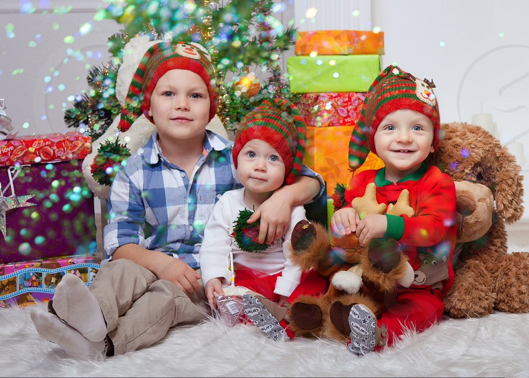 photo of boy in blue and white checked polo gray pants and sock beside toddler in white long sleeve red pants beside toddler in red and green cristmas suit in front of christmas tree photo
