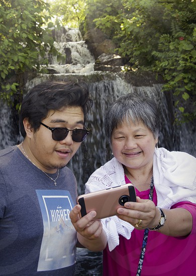 Mother and son family watching laughing reacting to social media on phone outside in a park with waterfall photo