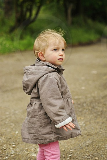 child in brown jacket and pink pants walking along a dirt road photo