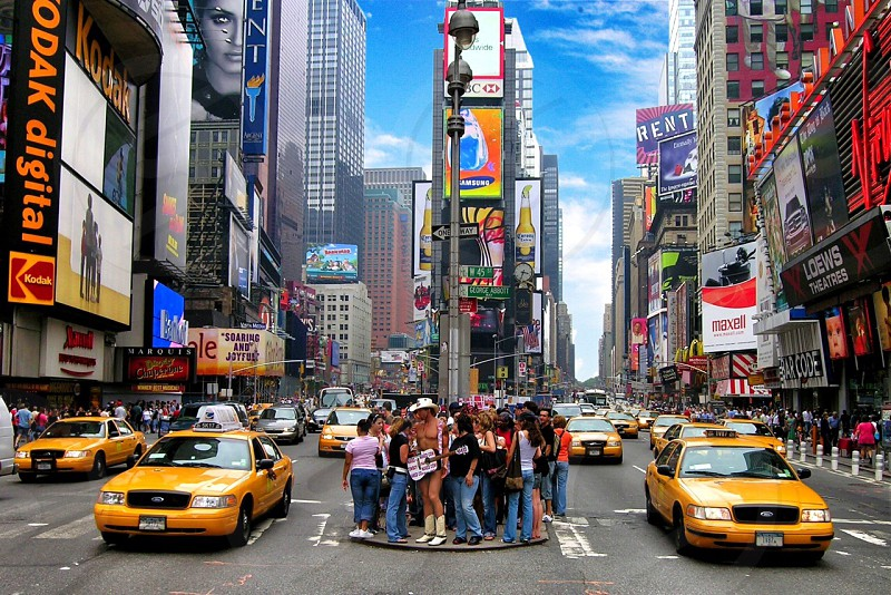 group of people standing on time square near taxi cabs photo