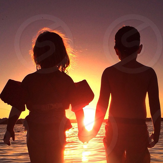 girl and boy holding hands standing near the water photo