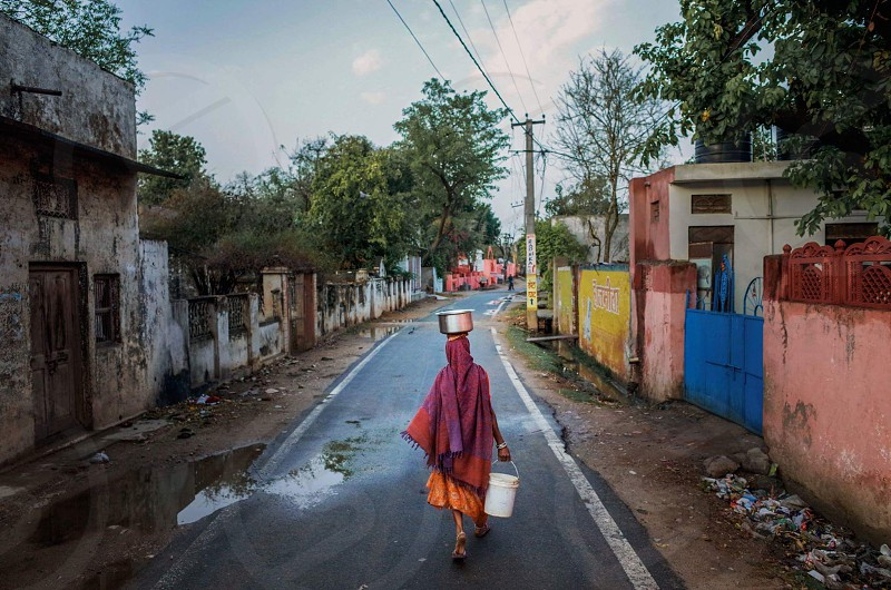 woman in red sari dress carrying white bucket on asphalt road during daytime photo