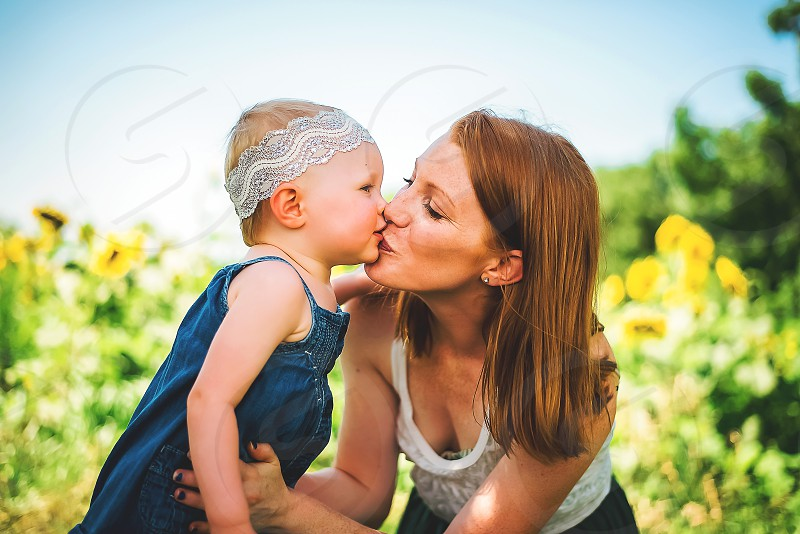 mom and daughter kiss in sunflower field photo