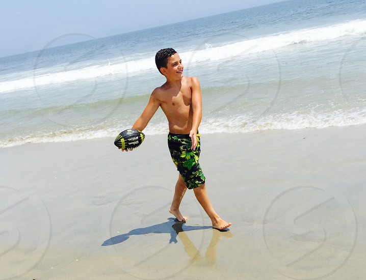 boy in green yellow and black camouflage board shorts holding football walking on beach shore photo