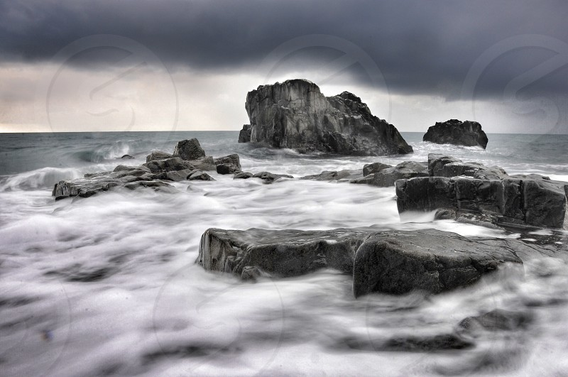 rocks in an ocean with fog on water photo