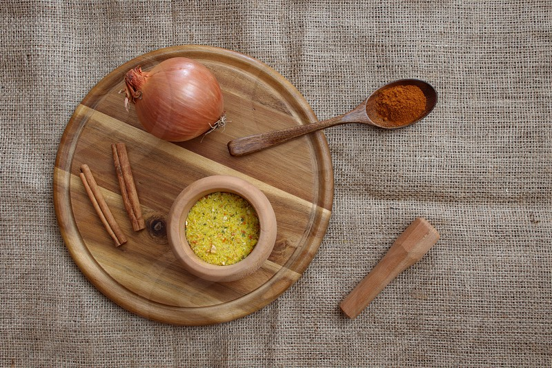 Spices in wooden bowl and wooden spoon onion and cinnamon on the wooden cutting board. Directly above shot photo