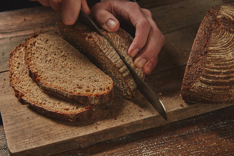 male chef's hand present and cutting Rye bread with knife on a wooden board photo