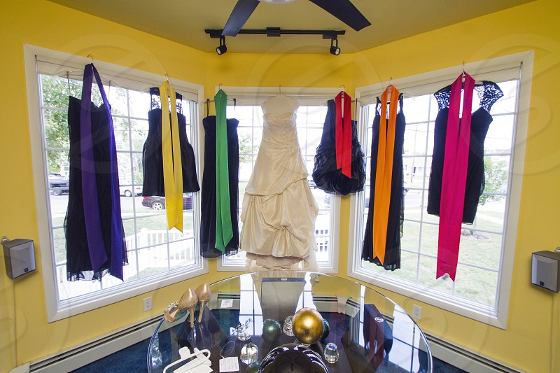 wedding gown and bridesmaids dresses hanging on a bay window photo