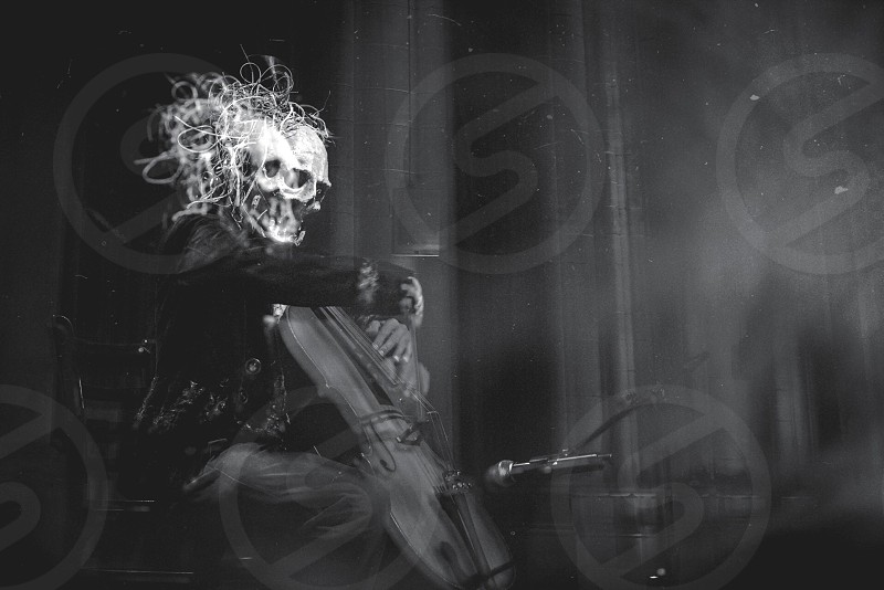 grayscale photography man in skull mask playing cello photo