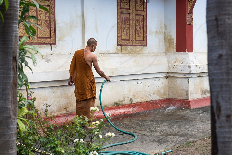 Buddhist monk listening to music on headphones while smoking a cigarette and cleaning his temple in Thailand. photo