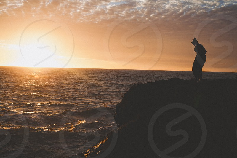 person standing on rock formation beside sea photo