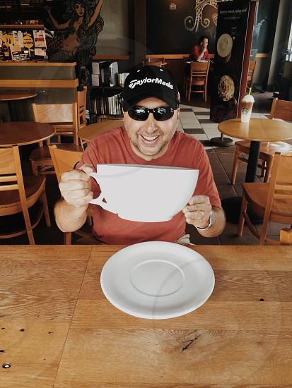 man holding a large white ceramic teacup photo