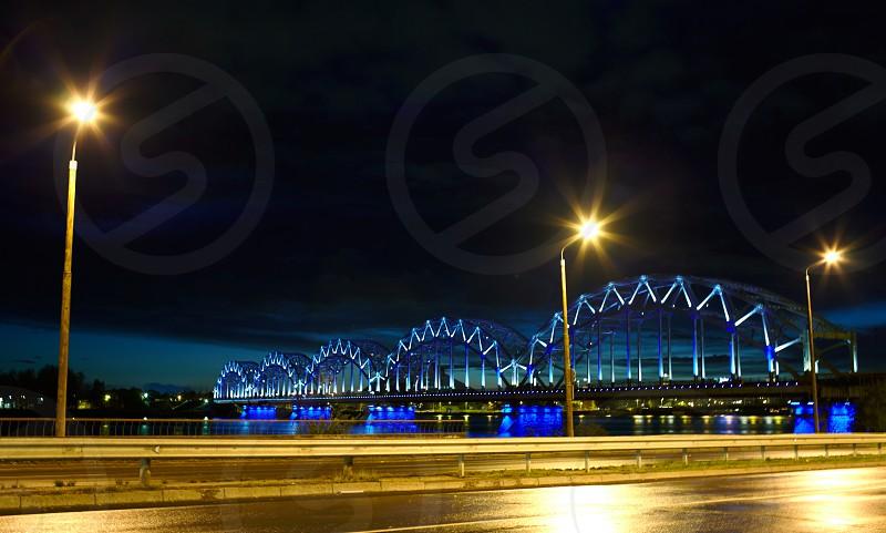 Railway bridge at night with citylights and dark sky. photo