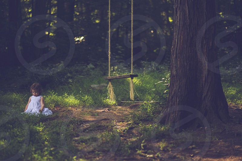 girl in white dress sitting on grass near swing photo