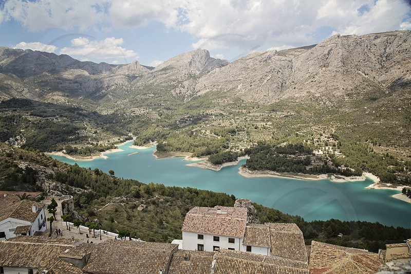 Blue waters at a lake in Valencia Spain. Clear water red roofs and spectacular mountains.Sutable for travel tourism adventure outdoors. photo