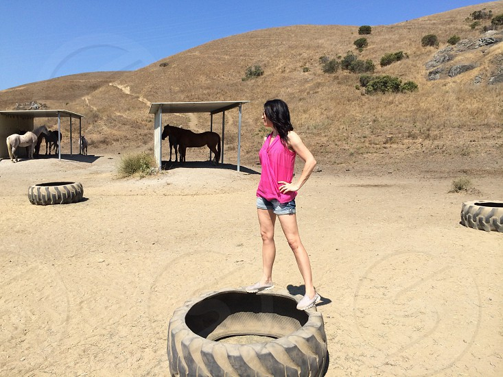 woman in pink v-neck sleeveless top and blue cuff shorts standing on vehicle wheel near team of horses photo