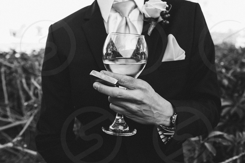 person wearing a suit with rose holding a wine glass photo