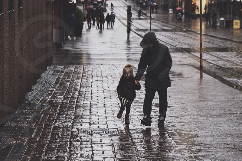 person holding girl while walking on sidewalk photo
