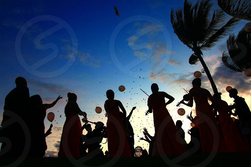 silhouette of people holding balloon under blue white cloudy sky photo