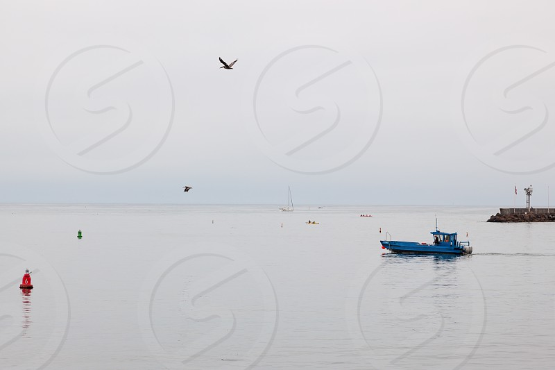 Blue boat slipping out of Santa Barbara harbour photo