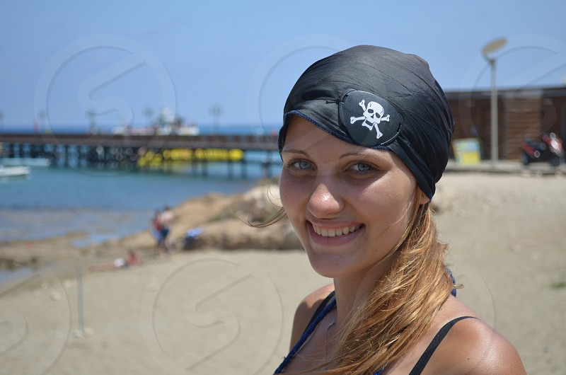 woman in black skull patched bandana smiling at camera photo