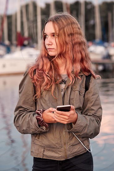 Young woman using mobile phone smartphone standing on a pier over a lake. Candid people real moments authentic situations photo