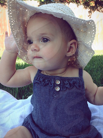 baby in blue denim shirt and a white hat photo