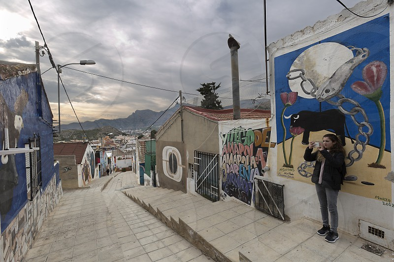 Orihuela Spain. February 26 2018: Young girl taking a picture with her mobile to the Murals of San Isidro in Homage to Miguel Hernandez in the city of Orihuela province of Alicante Spain. photo