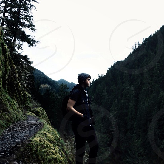 man in black button down shirt and black beanie standing in cliff photo