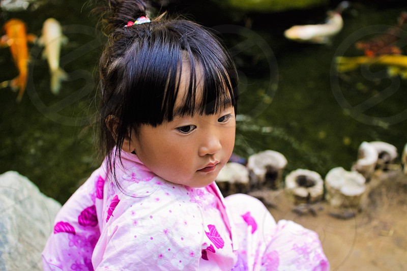 selective focus of girl in pink overall dress sitting near fish pond during daytime photo