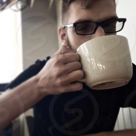 Young adult male drinking a cappuccino in a cafe coffee house. photo