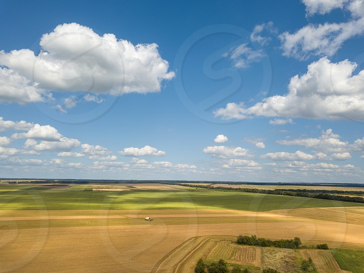 Bird's eye view of rural countryscape with clouds on a blue sky background in a summer sunny day. Aerial view from drone. photo