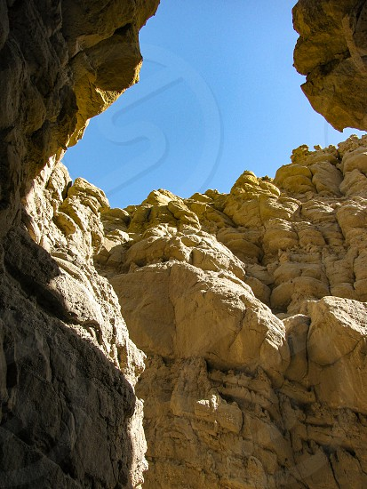 Rugged cliff walls and blue sky view looking up from bottom of deep slot canyon trail Anza Borrego Desert State Park California  photo