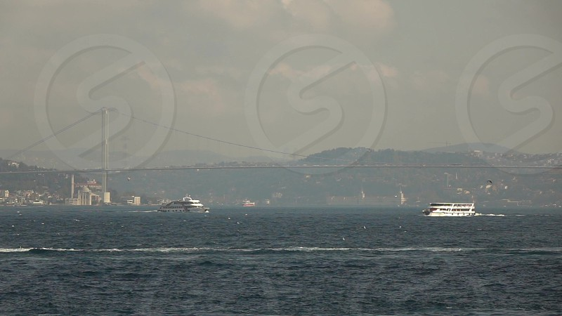 Picturesque seascape to 15 July Martyrs Bridge in Bosphorus strait with shiping traffic in a sunny summer day with cloudy sky. Panoramic slow motion Full HD video 240 fps 1080p. photo
