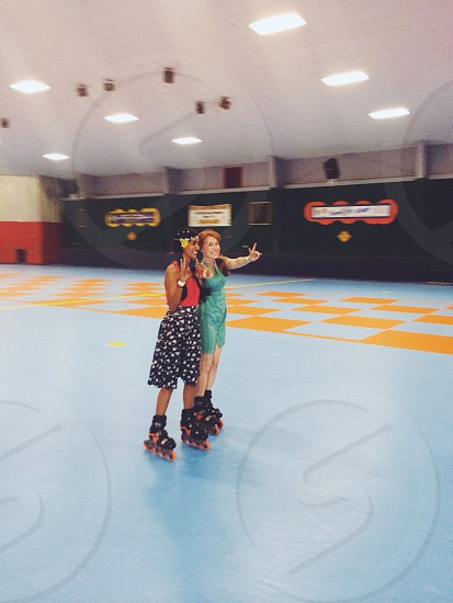 Two girls rollerblading and skating at a roller skating rink. Holding up peace signs wearing a dress and a skirt.  photo