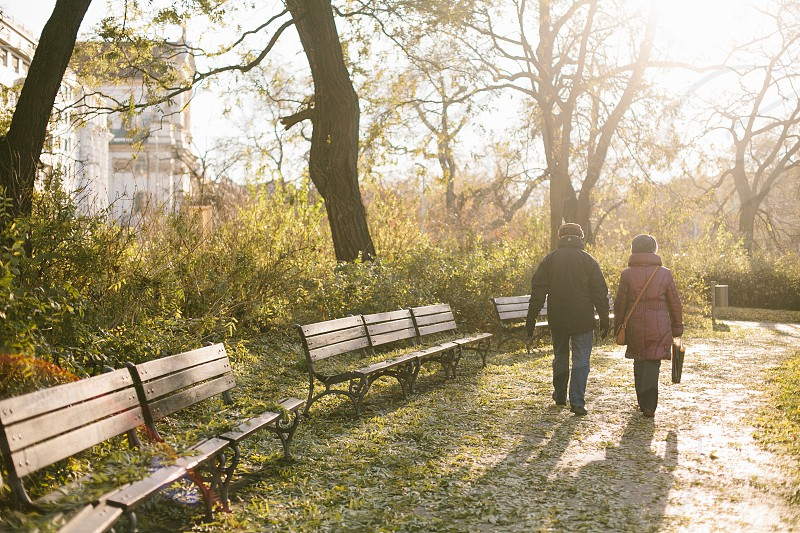 Man and woman strolling through a park in Prague during golden hour. photo