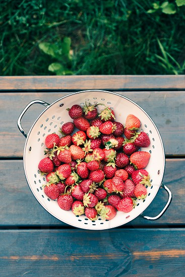 Closeup of bowl of fresh strawberries sprinkled raindrops on wooden table photo