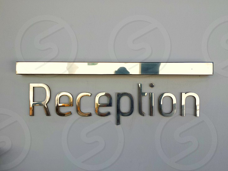 """Gold coloured metallic """"Reception"""" sign on a grey tinted white background... photo"""