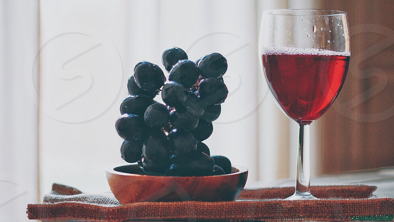 grape fruit on brown wooden saucer near clear wine glass with red liquid photo