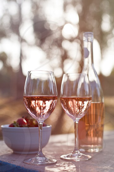 selective focus photography of 2 clear wine glass with beverage near white ceramic bowl with strawberries photo