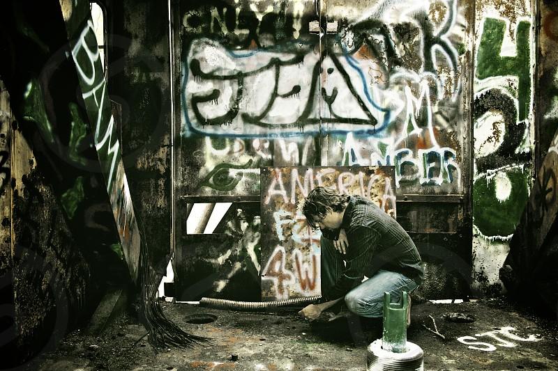man adding his mark to graffiti art in a machine photo