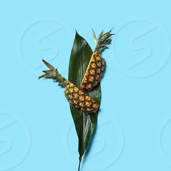 Healthy pineapple slices and green leaf on a dark blue background with space for text. Creative food composition. Flat lay photo
