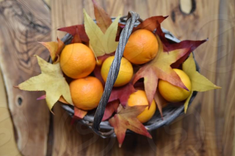 gray woven basket with orange citrus fruits photo