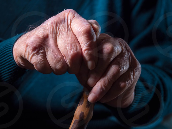 wrinkled old man' hands crossed on the stick. Close-up of a pensive grandfather sitting alone outdoors and rests on a cane. photo